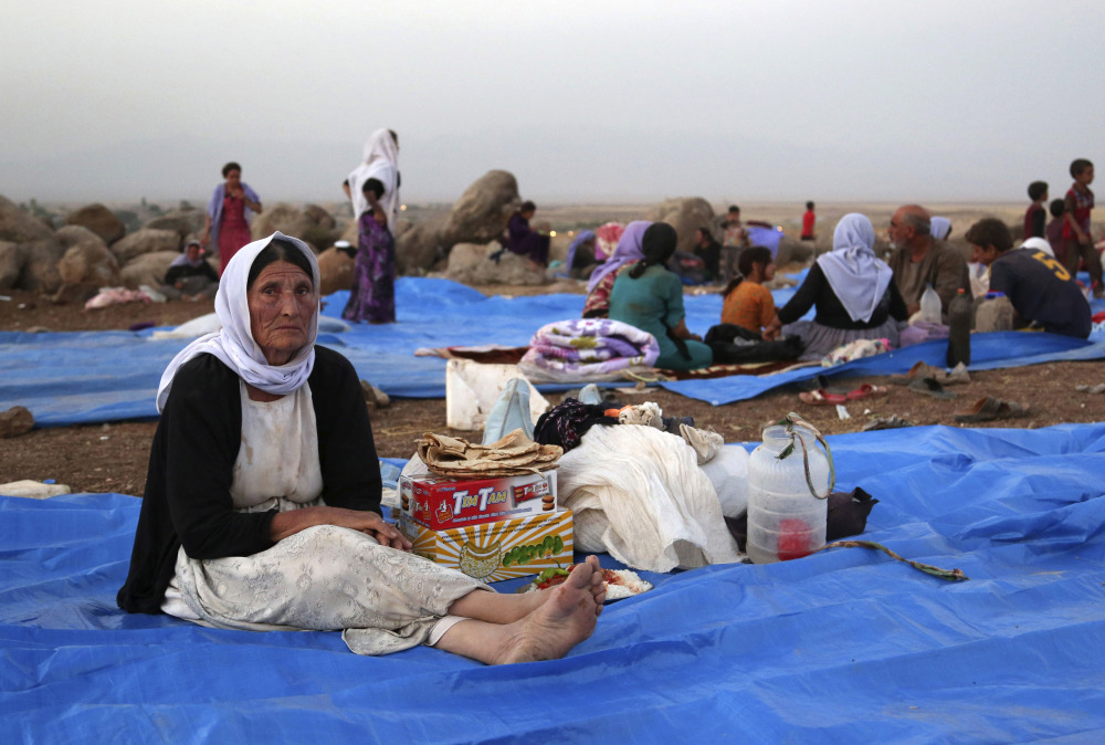 Displaced Iraqis from the Yazidi community settle at a camp at Derike, Syria. Syrian Kurds say they've rescued tens of thousands, transporting them into Syrian territory to give them first aid, food and water.