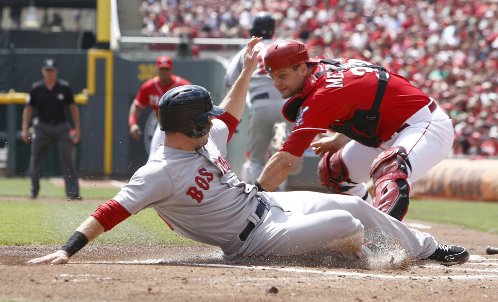 Boston Red Sox' Daniel Nava, left, scores in front of Cincinnati Reds catcher Devin Mesoraco, right, after a Mike Napoli ground ball in the first inning of a baseball game, Wednesday, in Cincinnati.