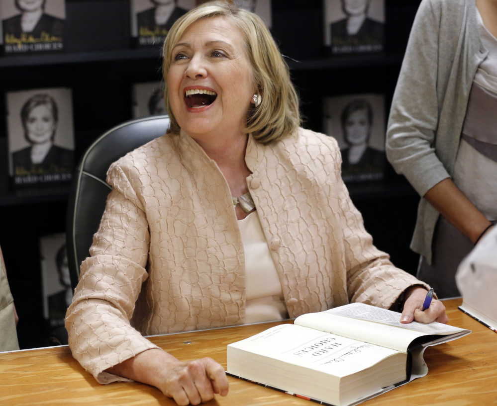 """Former Secretary of State Hillary Rodham Clinton laughs while speaking with a customer at a signing for her book """"Hard Choices,"""" at Bunch of Grapes Bookstore, Wednesday in Vineyard Haven, Mass."""