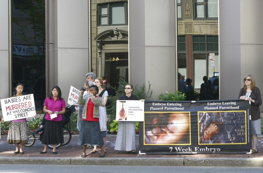 Anti-abortion protesters stand across the street from the Planned Parenthood clinic at 443 Congress St. in Portland. The city's 39-foot no-protest buffer zone was lifted July 7.