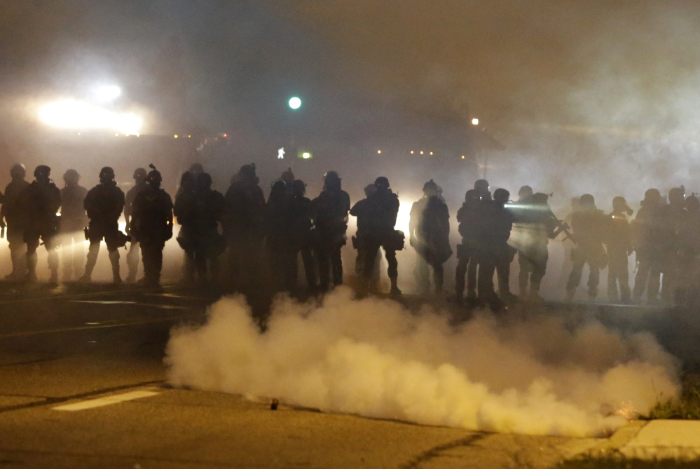 """Police advance through smoke Wednesday night in Ferguson, Mo. """"An undertow (of racial unrest) has bubbled to the surface,"""" said Police Chief Thomas Jackson."""
