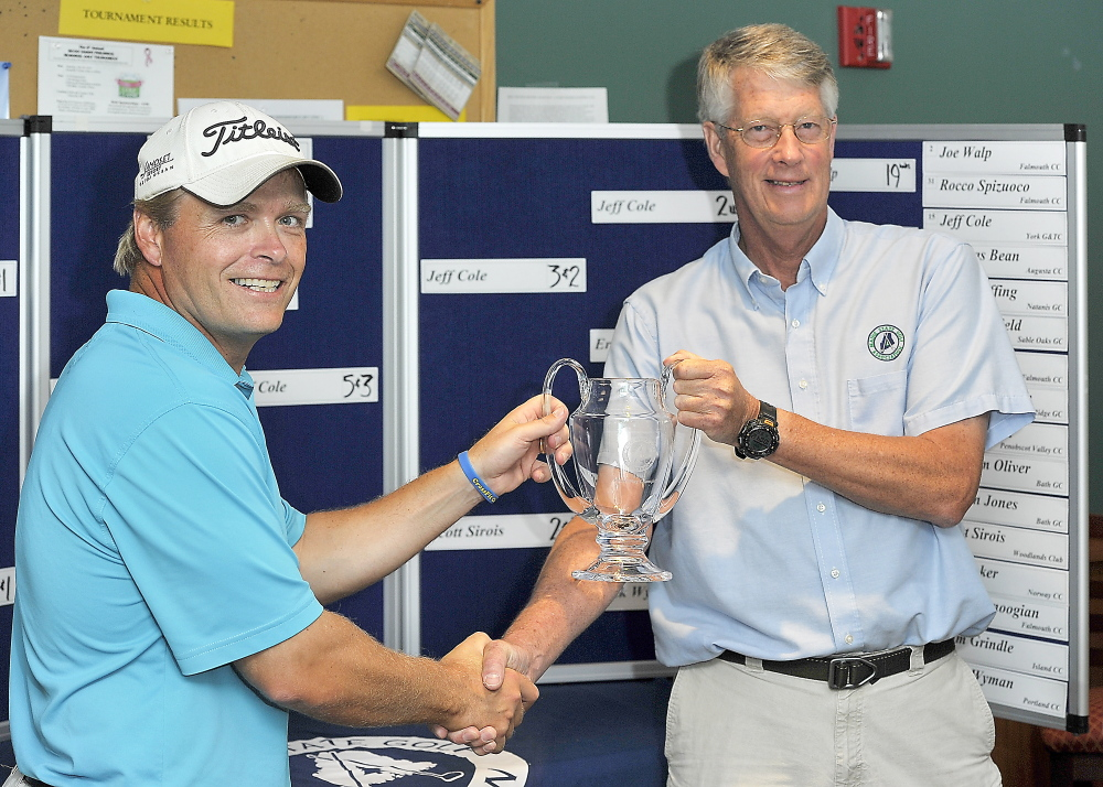 Ricky Jones, left, accepts the trophy from Randy Hodsdon, director of rules and competition, for his 6-and-4 defeat of Jeff Coles to win the Maine Match Play Golf Tournament played at Sable Oaks Golf Course.