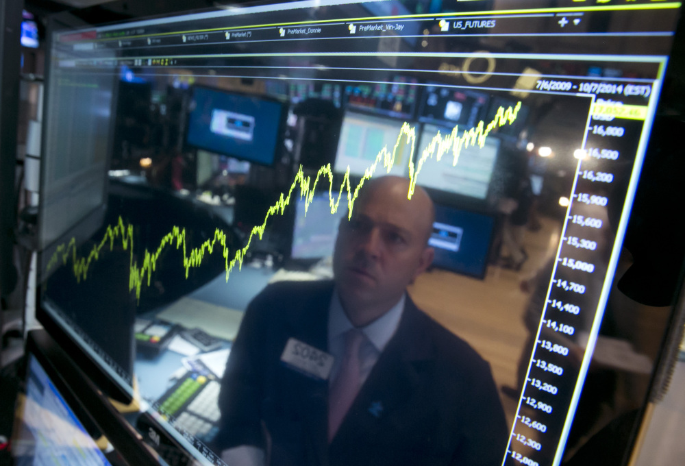 Specialist Jay Woods is reflected July 3 in a screen at his post that shows five years of the Dow Jones industrial average, on the floor of the New York Stock Exchange.