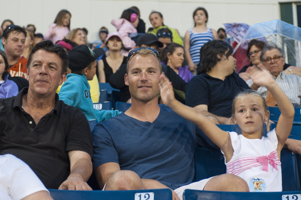 From left, Tom Sheehan, Barry Hertzler and his daughter, Emersyn Hertzler, watch a Sea Dogs game. Sheehan was the host family for Hertzler for three seasons.