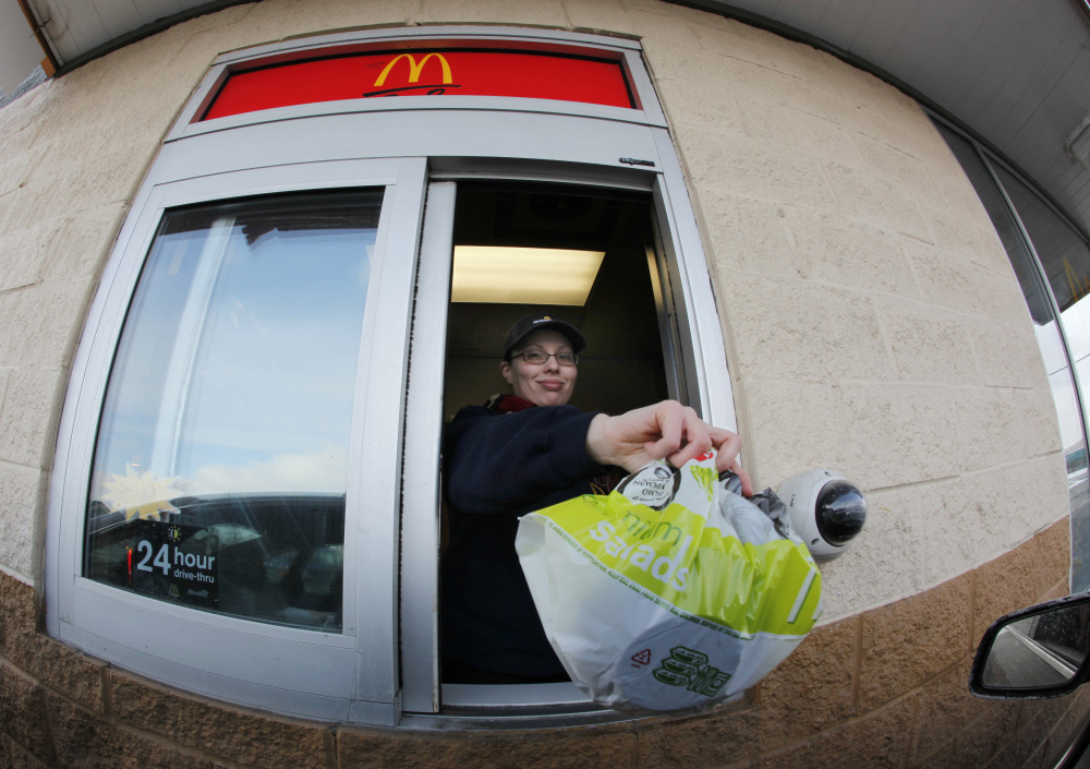 McDonald's employee Cortney Sobowiec hands a patron a salad at the drive up window at McDonalds in Williamsville, N.Y.