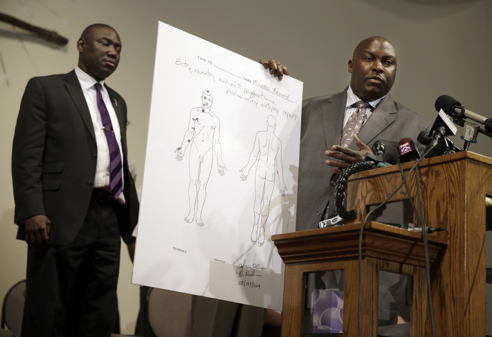 Attorneys Daryl Parks, right, and Benjamin Crump share preliminary results of a second autopsy done on Michael Brown, Monday in St. Louis County, Mo.