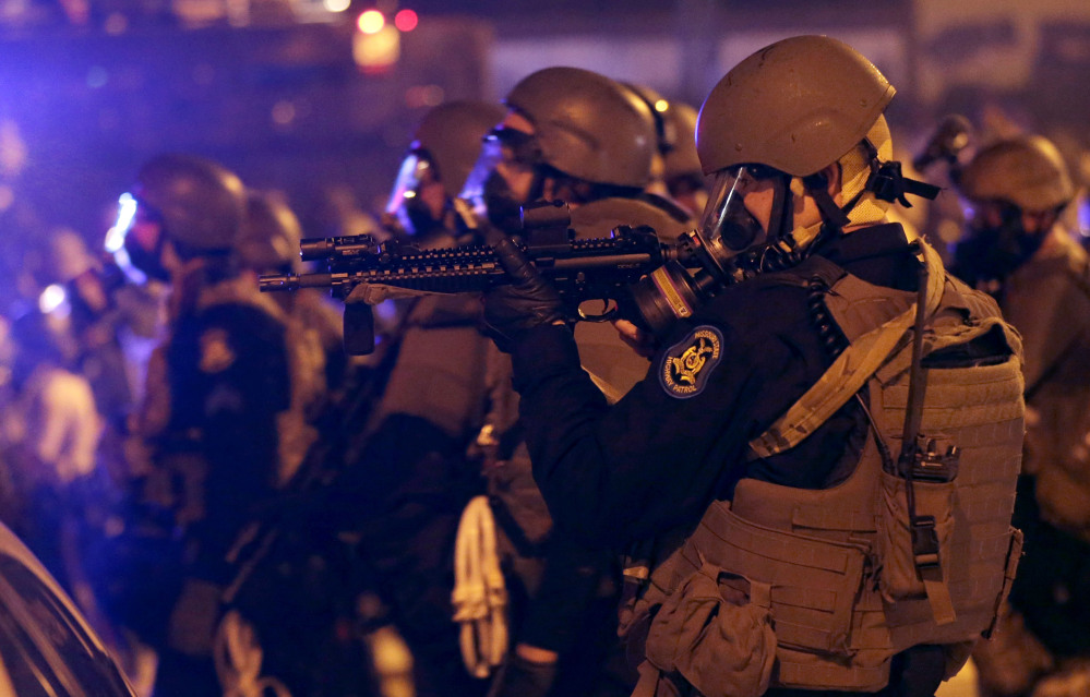 Police advance after tear gas was used to disperse a crowd Sunday during a protest over an officer's killing of a black teen in Ferguson, Mo.   The Associated Press