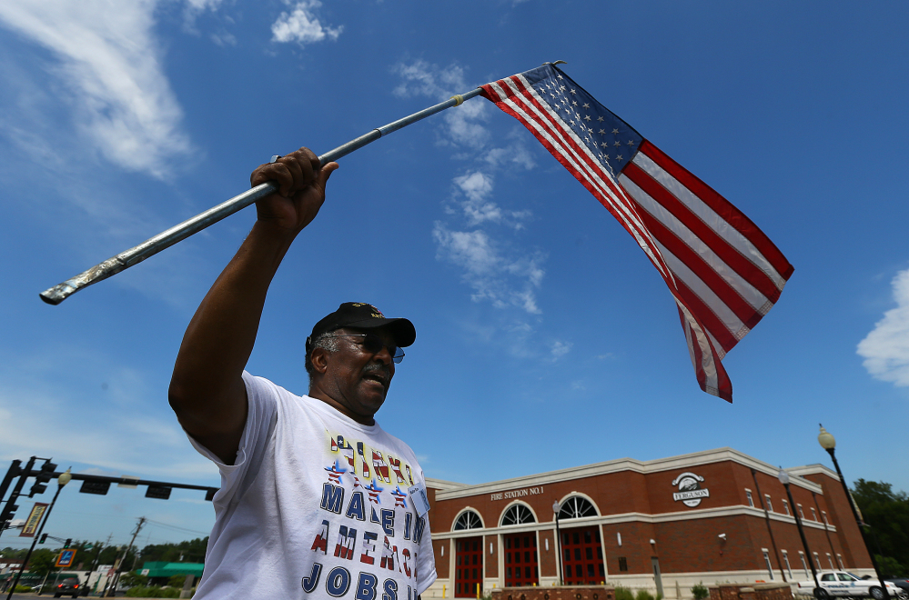 Walter Rice, 75, a life-long Ferguson resident and a Vietnam veteran, waves an American flag as he protests Tuesday in front of the Ferguson police department.