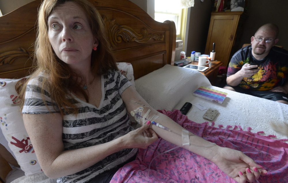 Lisa Lawlor of Saco adjusts her IV as she takes antibiotics, part of her routine to manage her many Lyme disease-related symptoms. Her friend Lee Faulkner of Saco is at her bedside. She noticed a rash in 2011, but was not diagnosed until 2013.