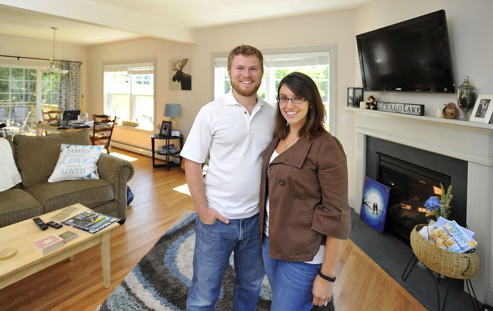 """Rob and Samantha McNamee pose in the home they built in Sebago Heights Estates in Windham. """"Our money goes a lot farther in Maine than in Massachusetts,"""" Rob McNamee says."""