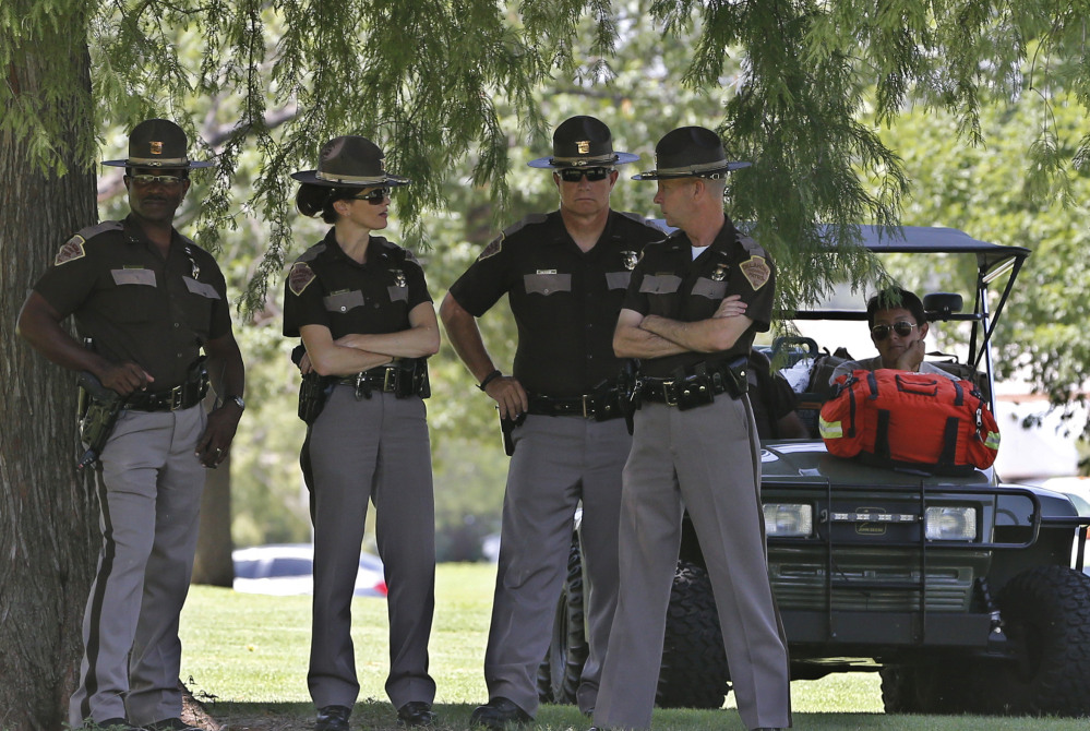 Oklahoma Highway Patrol officers watch from a distance under the shade of some trees during a rally at the state Capitol in Oklahoma City on Thursday. The rally was in response to the shooting death of 18-year-old Michael Brown in Ferguson, Mo.