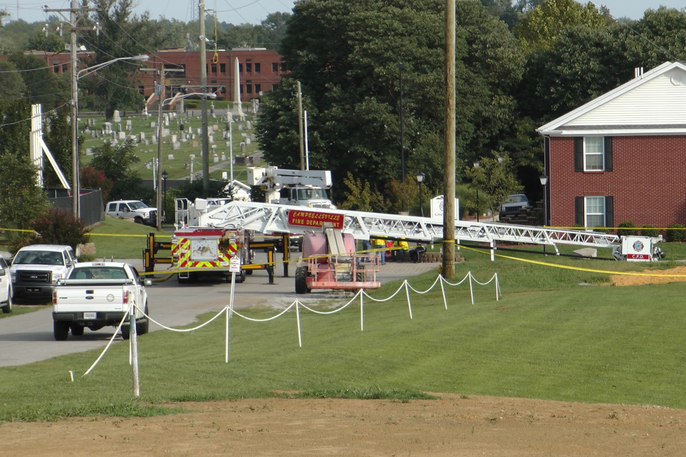 A Campbellsville Fire Department truck with the ladder extended remains at the scene where four firefighters were injured after an ice bucket challenge during a fundraiser for ALS on Thursday in Campbellsville, Ky. Officials say the ladder got too close to a power line and electricity traveled to the ladder. The Associated Press