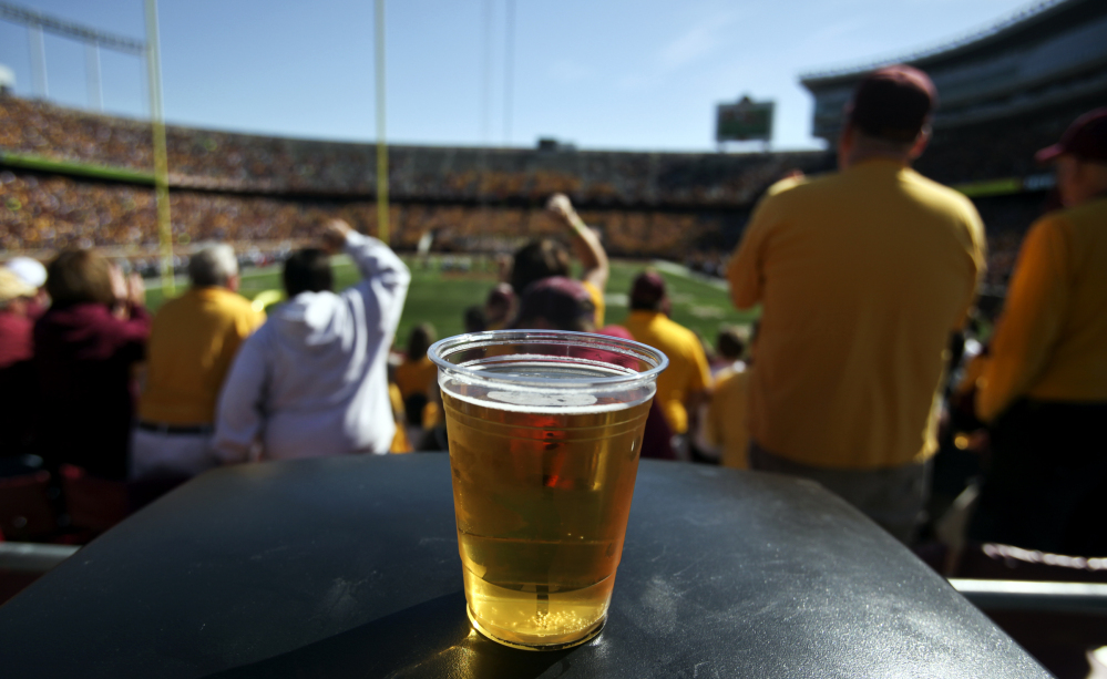 A beer sits atop a garbage can as Minnesota college football fans cheer a play against New Hampshire at TCF Bank Stadium in Minneapolis, Minn., in September 2012. A growing number of schools are capitalizing on fans' taste for the suds.