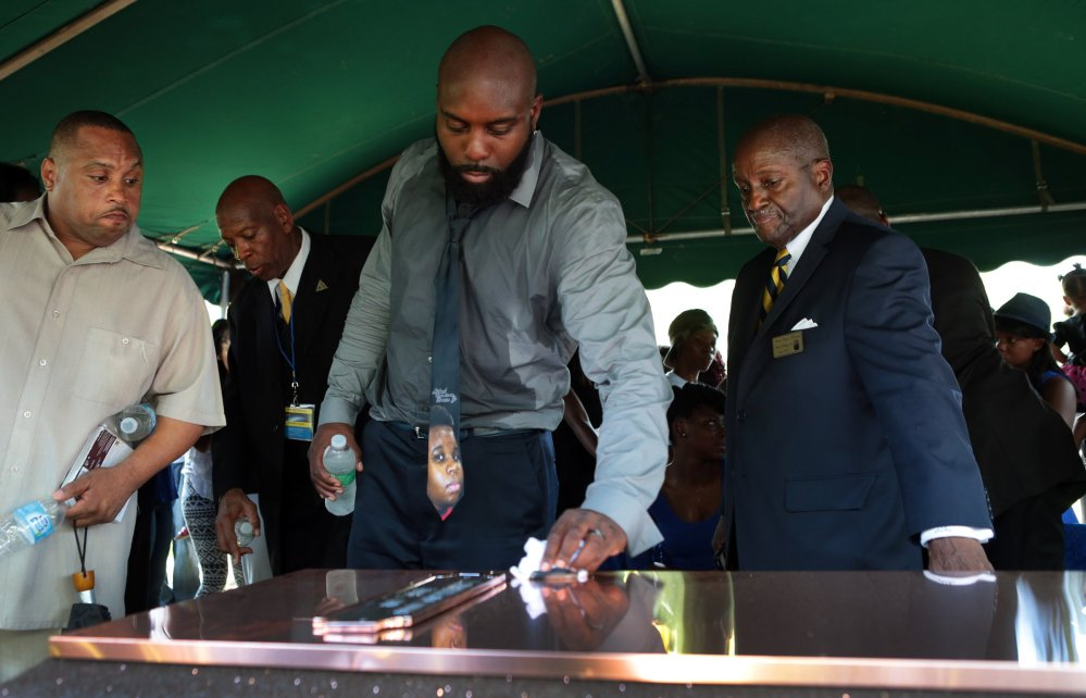 Michael Brown, Sr. wipes the top of the vault containing the casket of his son Michael Brown, Monday in Normandy, Mo. Hundreds of people gathered to say goodbye to Brown, who was shot and killed by a Ferguson, Mo., police officer on Aug. 9.