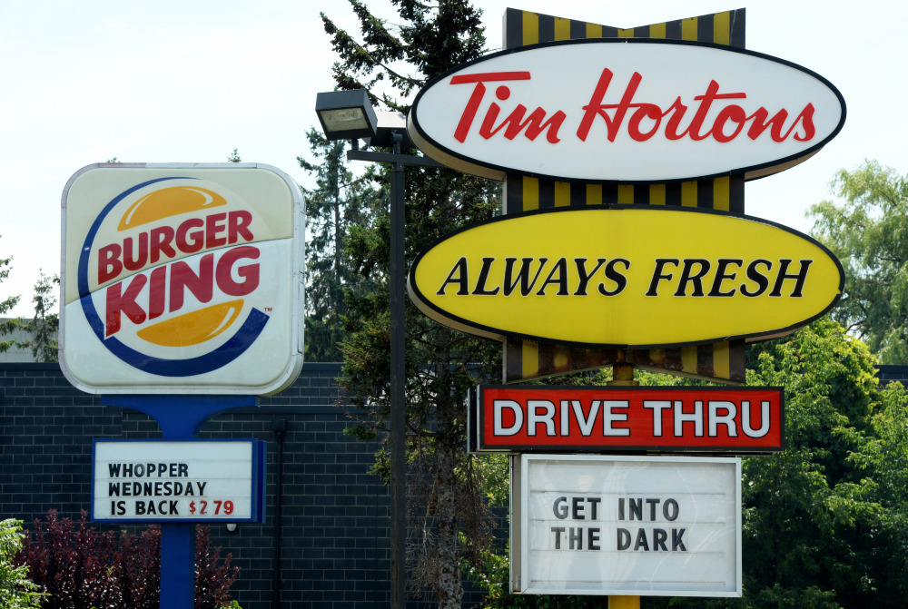 A Burger King sign and a Tim Hortons sign are displayed on St. Laurent Boulevard in Ottawa, Canada, on Monday.