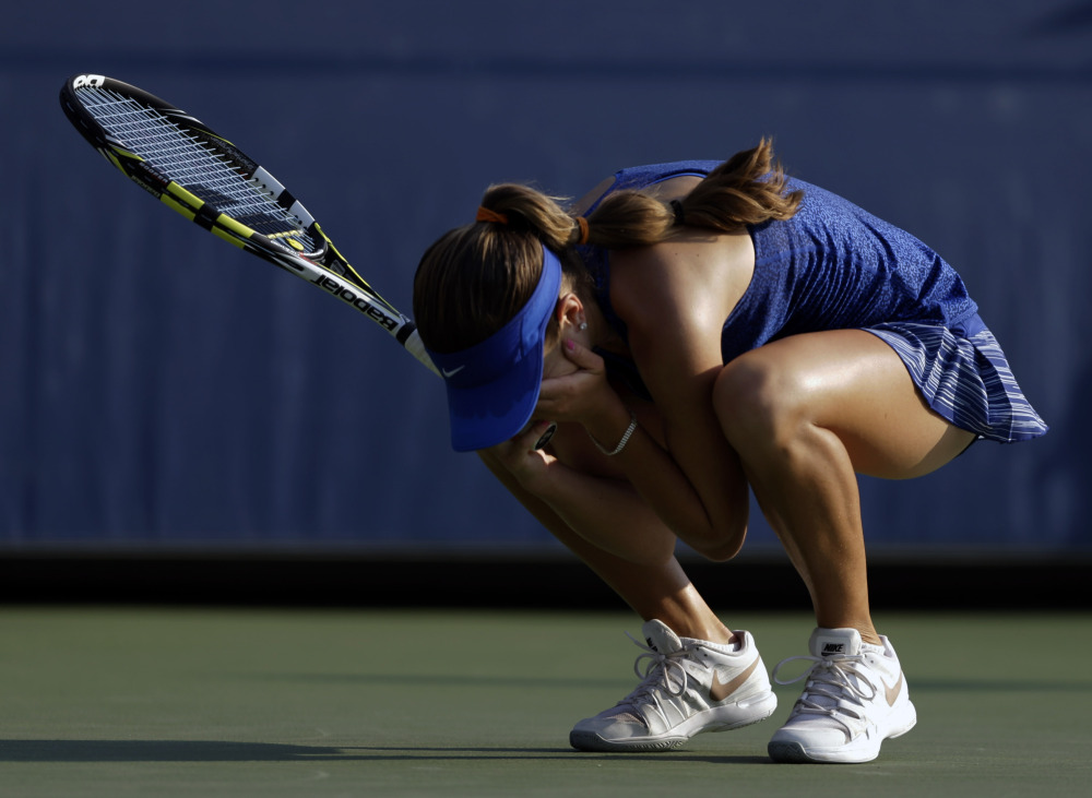 Catherine Bellis drops to her knees after defeating Dominika Cibulkova and becoming the youngest player to win a U.S. Open match since 1996.