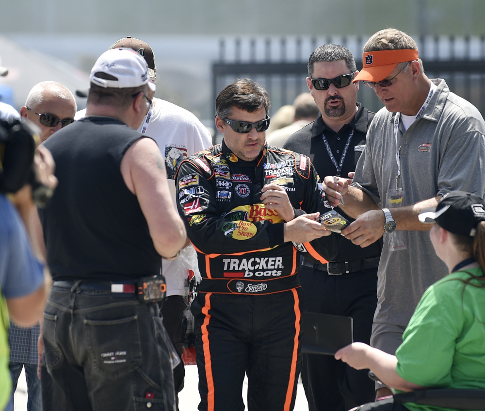 NASCAR driver Tony Stewart signs autographs as he makes his way to his car to practice for Sunday's race at Atlanta Motor Speedway in Hampton, Ga., on Friday.