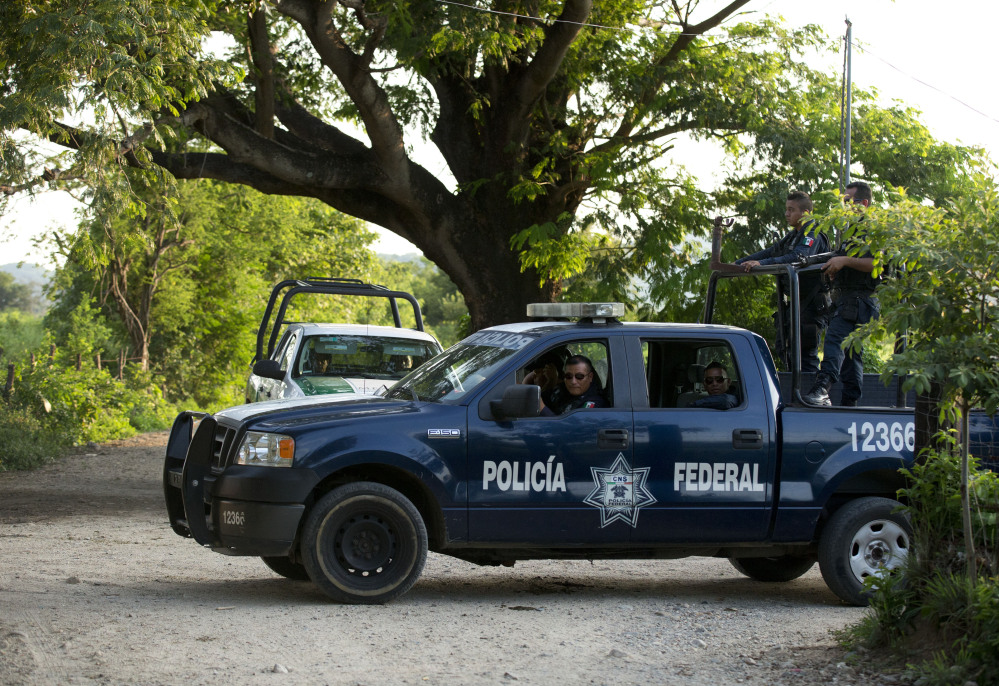 """Federal police and immigration vehicles patrol near the railroad tracks as a northbound freight train departs from Arriaga, Mexico. A crackdown seems to be keeping women and children off the train, known as """"The Beast."""""""