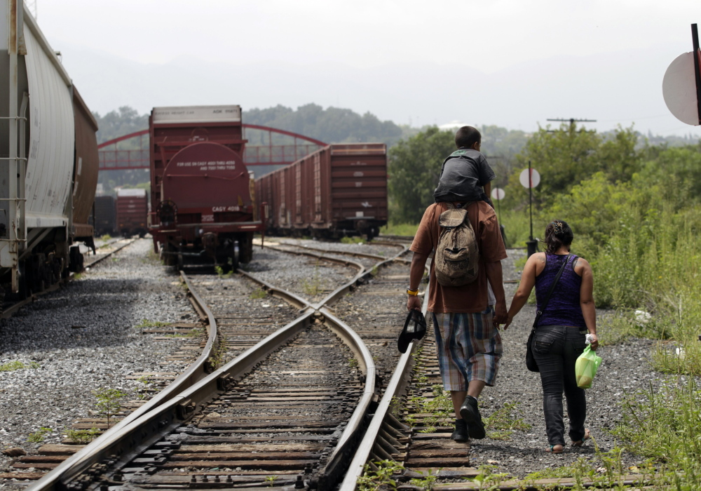 """A couple from El Salvador walk with their 3-year-old son on the train tracks in Saltillo early this month. The young family planned to catch the cargo train nicknamed """"The Beast"""" to the United States."""