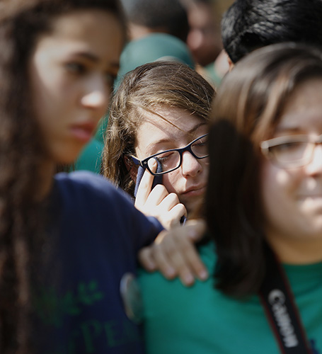 A camper wipes away a tear with her shirt while listening to speakers during opening ceremonies at Seeds of Peace. Derek Davis/Staff Photographer