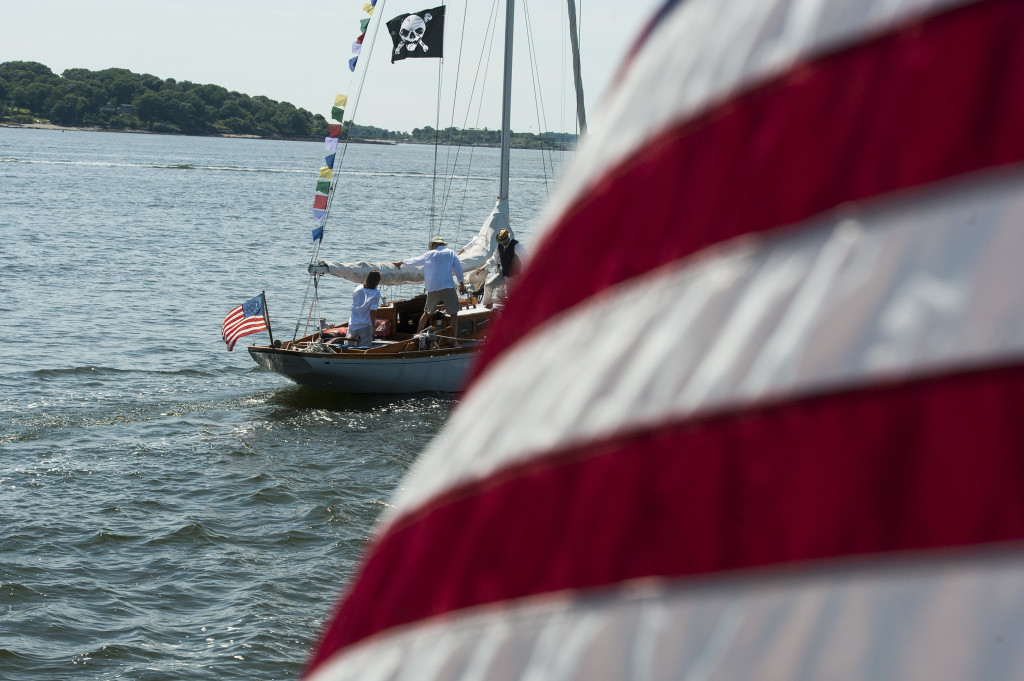 Boats decorated with flags sail through Portland Harbor before the first gun at the MS Harborfest Regatta on Saturday. Logan Werlinger/Staff Photographer