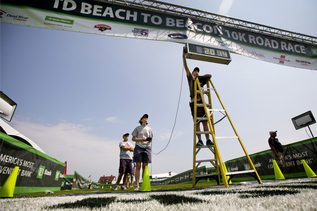 Bob Teschek, owner of Granite State Race Services, attaches a wire to the race clock after hanging it above the finish line of the TD Beach to Beacon 10k at Fort Williams Park on Friday.