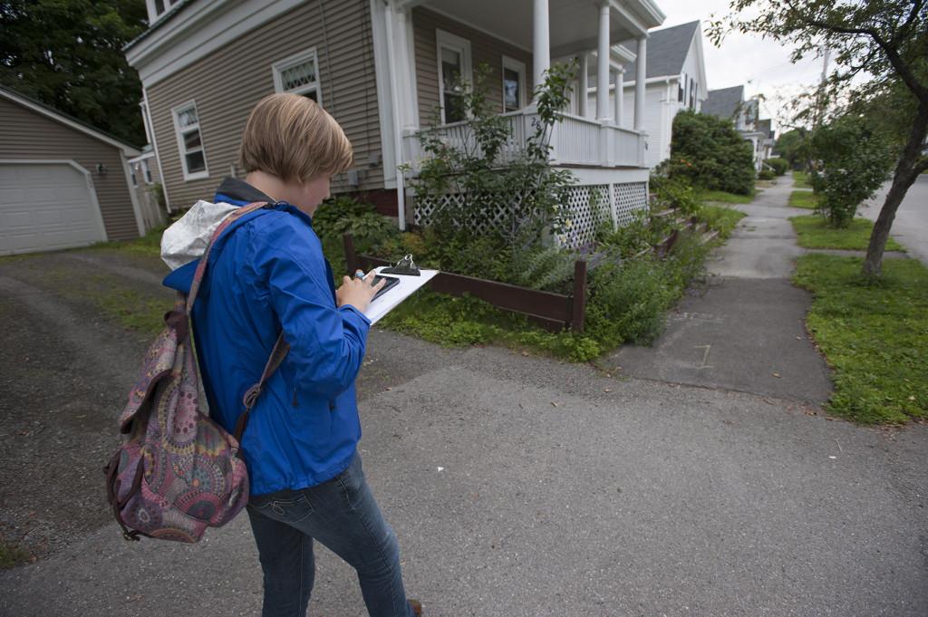 Howard checks her tablet as she walks up Maple Street in Bangor.