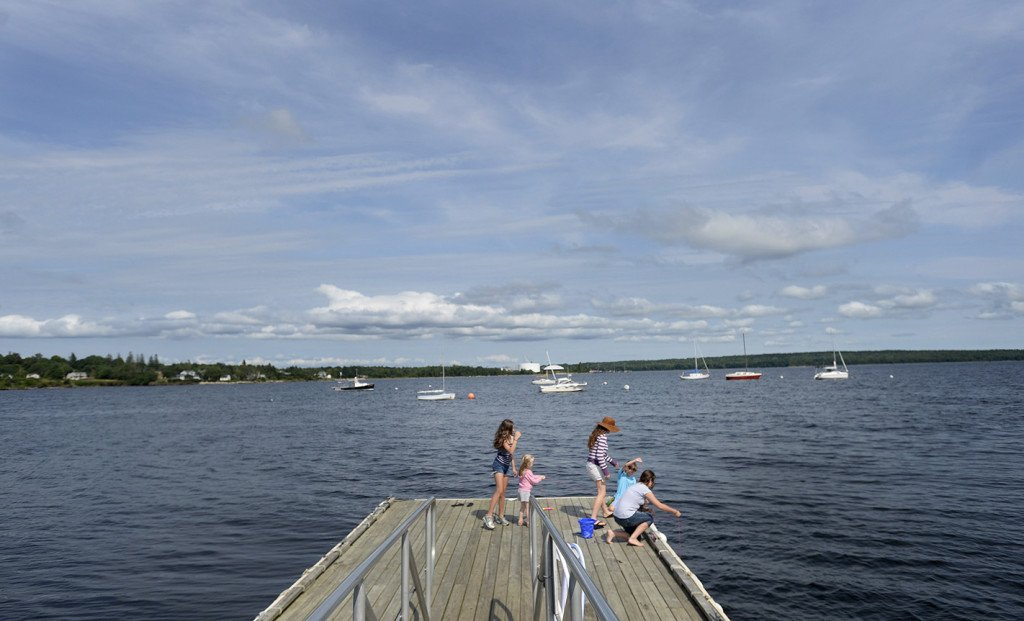 Children fish for crabs from the Searsport Public Landing with the Searsport Harbor in the background.