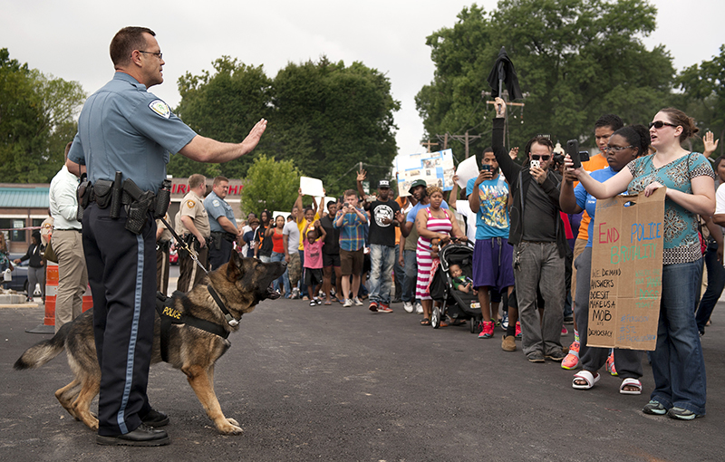 Protestors confront police during an impromptu rally, Sunday, to protest the shooting of Michael Brown, 18, by police in Ferguson, Mo.  Saturday. The Associated Press