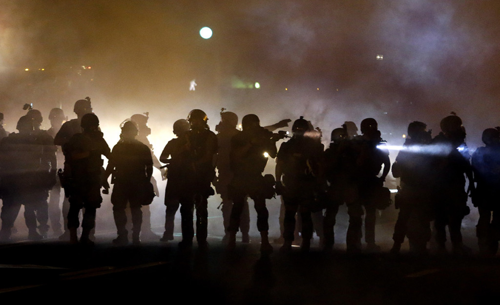 Police walk through a cloud of smoke as they clash with protesters Wednesday in Ferguson, Mo.  Protests in the St. Louis suburb rocked by racial unrest since a white police officer shot an unarmed black teenager to death turned violent Wednesday night, with some people lobbing molotov cocktails at police who responded with smoke bombs and tear gas to disperse the crowd.