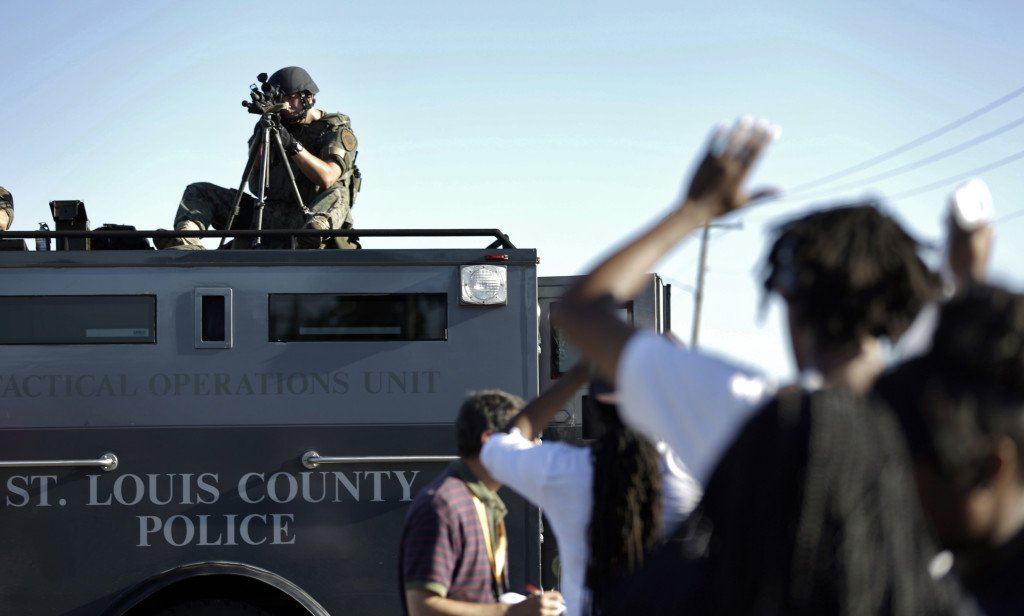 A member of the St. Louis County Police Department points his weapon in the direction of a group of protesters in Ferguson, Mo., on Wednesday as unrest continues over the fatal shooting of an unarmed black teenager.