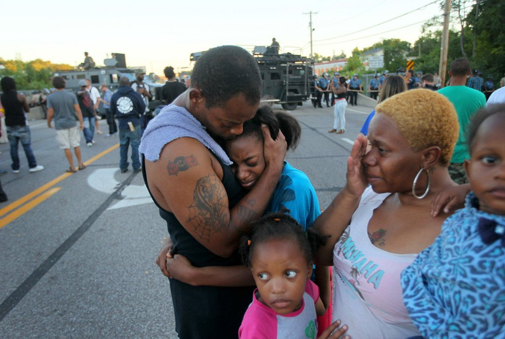 """Terrell Williams El hugs his daughter Sharell, 9, while standing with his wife, Shamika Williams, and daughters Tamika, 6, and Sharell, 2, on Wednesday in Ferguson, Mo. They were overcome with emotion after Williams El confronted police. """"I'm out here to stand for my children and their future,"""" said Williams El."""