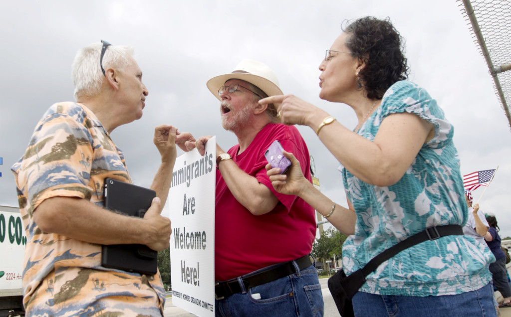 Reflecting the heated issue of the influx of children across the U.S. border, immigration supporters David Smith, center, and Rona Smith debate with a man opposed to illegal immigration on Saturday, in Conroe, Texas. The Associated Press