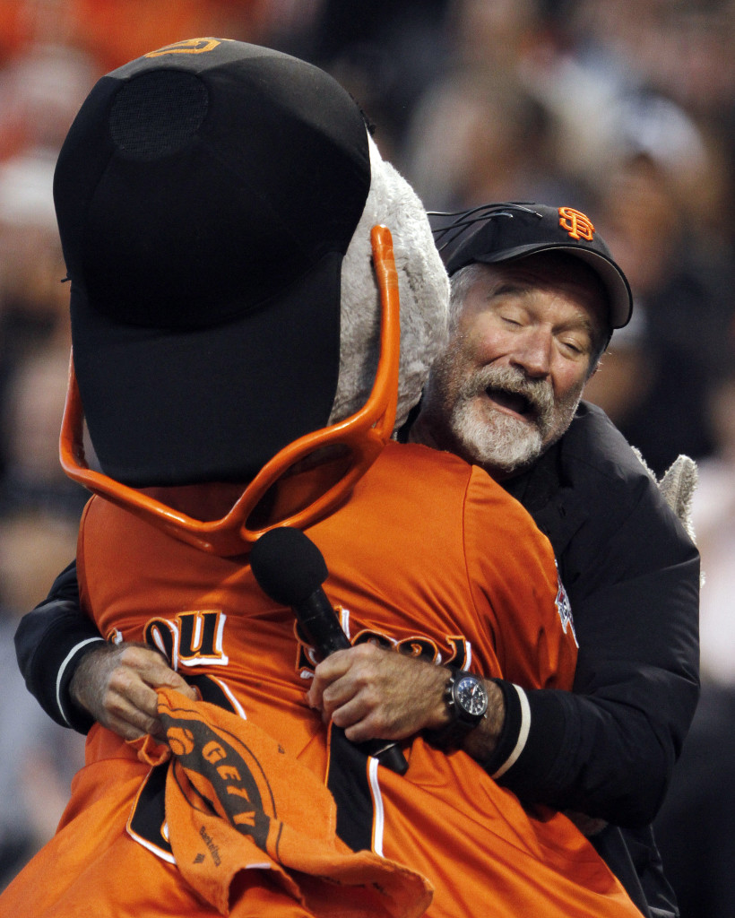 Robin Williams hugs the San Francisco Giants' mascot, Lou Seal, during Game 1 of the 2010 National League Division Series in San Francisco.