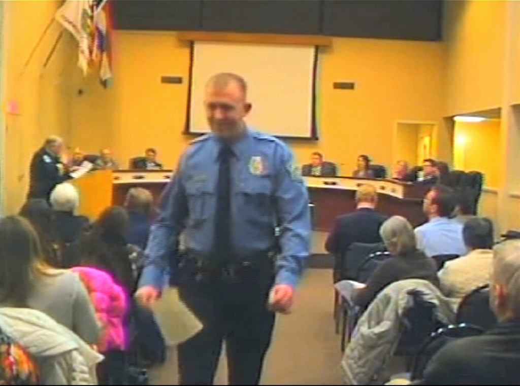 In this  Feb. 11, 2014 image from video released by the City of Ferguson, Mo., officer Darren Wilson attends a city council meeting in Ferguson.  Police identified Wilson, 28, as the police officer who shot Michael Brown on Aug. 9, 2014, sparking over a week of protests in the suburban St. Louis town. The Associated Press