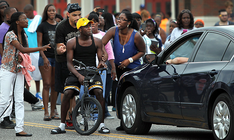 Protestors blocking Florissant Road block a motorist who tries to get through their sit-in in front of the Ferguson, Mo., police department on Sunday. The Associated Press