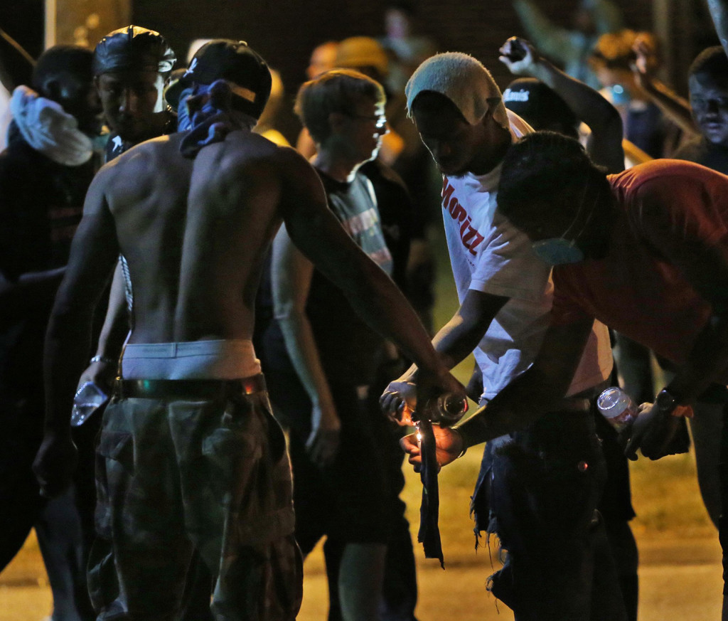 Protesters try unsuccessfully to light a Molotov cocktail Wednesday in Ferguson, Mo.