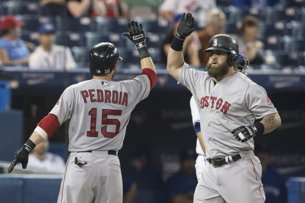 Boston Red Sox's Mike Napoli, right, is congratulated by Dustin Pedroia after hitting a three-run homer off Toronto Blue Jays pitcher Sergio Santos during the 11th inning of a baseball game Tuesday in Toronto.