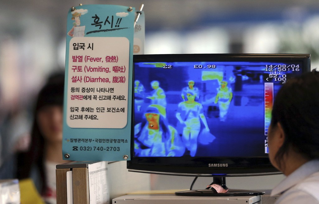 In South Korea, a quarantine officer at the Incheon International Airport checks a thermal camera showing the body temperature of passengers arriving from West Africa and other areas affected by the deadly Ebola virus. The Associated Press