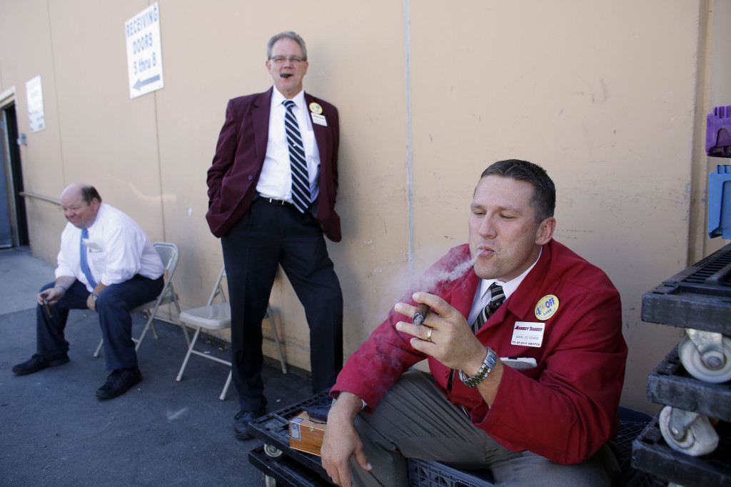 "Market Basket employees, from left, Bob Chausse of Dracut, Mass., Kevin Feole of Methuen, Mass., and Jamie Cunneen of Haverhill, Mass., smoke what Feole described as ""victory cigars"" behind a Market Basket supermarket Thursday  in Chelsea, Mass."