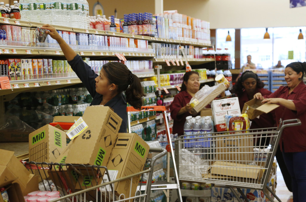 Market Basket employee Andrea Mejia of Methuen, Mass., left, works with other employees as they restock shelves at a Market Basket supermarket Thursday in Chelsea, Mass.