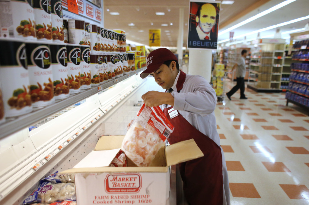 Market Basket employee Melbi Peraza of Chelsea, Mass., restocks frozen shrimp at a Market Basket supermarket Thursday in Chelsea, Mass.