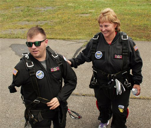 Staff Sgt. Travis Mills walks with first lady Ann LePage prior to their parachute jump over Fort Kent on Saturday. Mills, who suffered wounds in Afghanistan that cost him both arms and legs, made the jump to raise money for a veteran center and museum in Fort Kent. The Associated Press/All Veterans Group