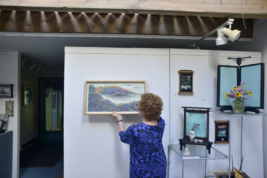 Kuhl hangs a piece of artwork in her gallery at Widgeon Cove Studios. Kuhl makes paper and combines different pigments to create landscapes and other artwork.