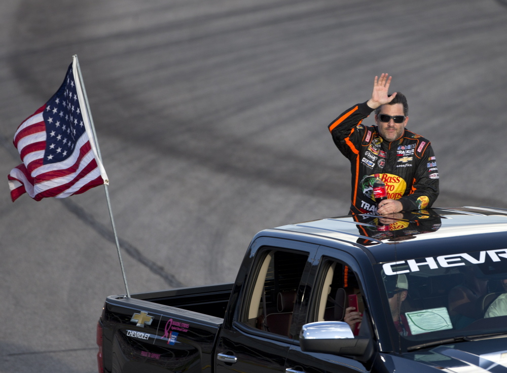 Tony Stewart waves to the crowd before the start of the Sprint Cup race Sunday night at Atlanta Motor Speedway. Stewart, in his first race since Aug. 3, didn't complete the race because of two crashes and finished 41st.