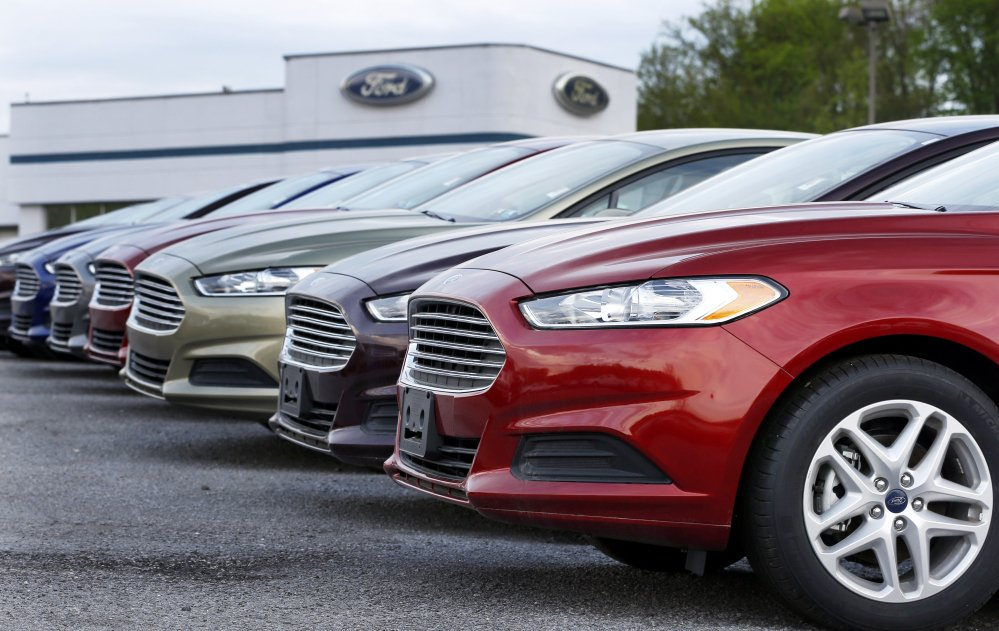 In this Wednesday, May 8, 2013 file photo, a row of new 2013 Ford Fusions are on display at an automobile dealership in Zelienople, Pa.