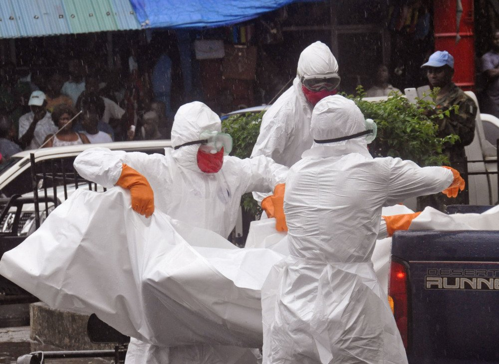 Health workers load the body of a man  suspected of dying from the Ebola virus onto the back of a truck on a busy street in Monrovia, Liberia, Tuesday. The number of deaths in West Africa has now surpassed 1,900.