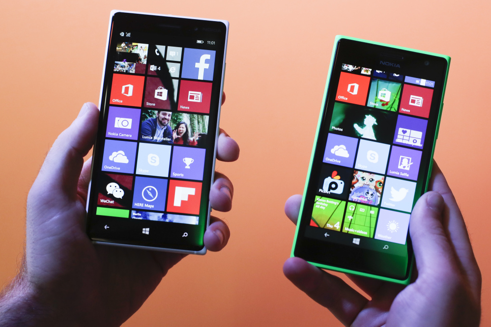 A man shows the new Lumia 830, left, and 730, right, smart phones during a Microsoft Nokia presentation event at the consumer electronic fair IFA in Berlin.
