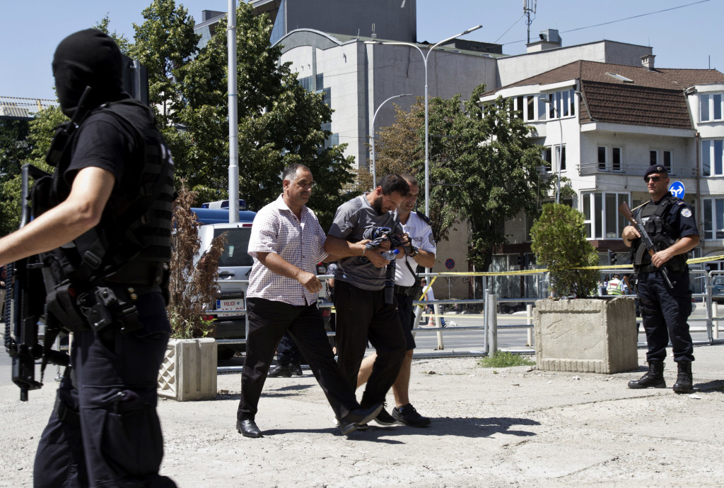 Kosovo police escort a Kosovo Albanian man suspected of fighting alongside Islamic radicals in Iraq and Syria to a local court in Pristina Aug. 12, 2014. Kosovo police on arrested at least 40 people in a major operation targeting Islamic radicals suspected of fighting alongside extremists in Iraq and Syria. The Associated Press
