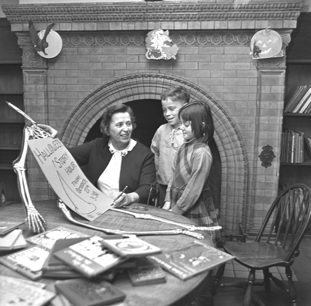 From the Oct. 30, 1967 Portland Press Herald. Photo by Staff photographer Johnson. Mrs. Mariana Rowe, Children's Librarian, with seven-year-old Jerry Amerigian and eight-year-old Suzanne Modes, both of Sherman Street, at a Halloween party held at the Portland Public Library's Baxter Building at 619 Congress Street, now the headquarters of the Via Agency.